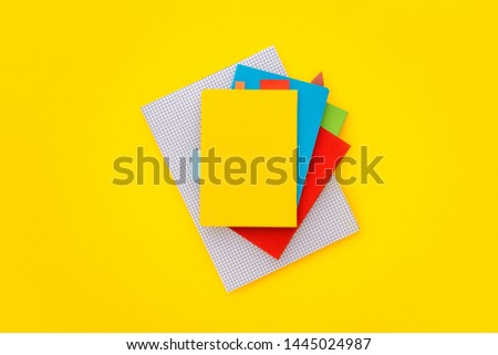 Blank notebook cover on a stack of notebooks on yellow background. Top view.