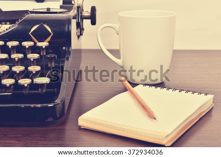 blank notebook, cup and  vintage typewriter  on the writer's desk