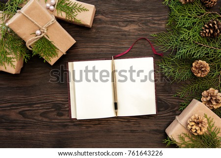Blank notebook gifts boxes branch and fir cones on wooden
