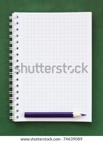 Blank notebook on green chalkboard - background - stock photo