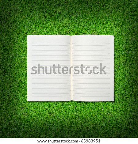 Blank notebook on Green Grass background.