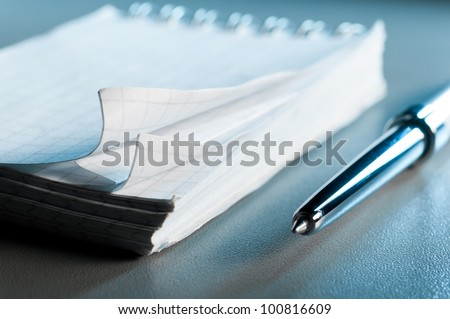 blank notebook on table with pen. Blue toned, shallow dof #100816609