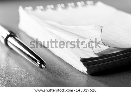 blank notebook on table with pen. Blue toned, shallow dof #143319628