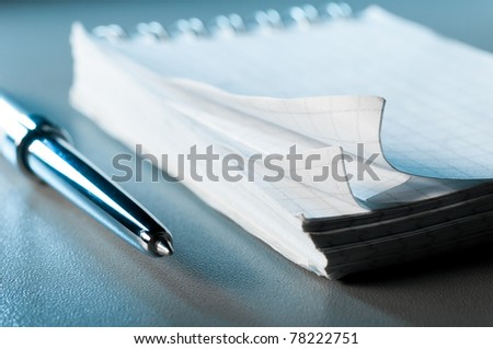 blank notebook on table with pen. Blue toned, shallow dof #78222751