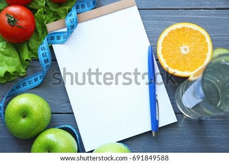 Blank notebook, pen and healthy food on wooden table. Weight loss concept
