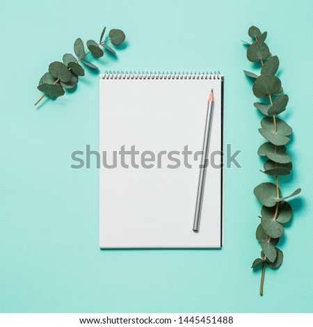 Blank notebook, pencil and eucalyptus on blue background. Empty notebook paper and eucalyptus branch on pastel blue background with copy space for text or design. Flat lay, top view, copyspace, square