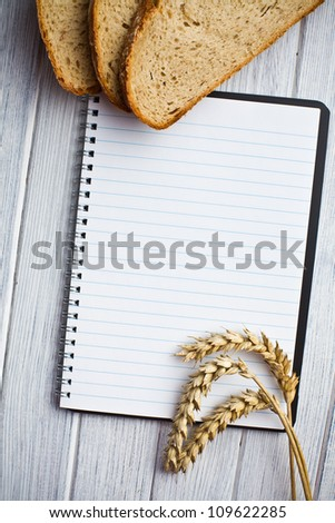 blank notebook with bread and wheat on wooden table