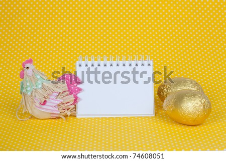 Blank notebook with Easter chocolate eggs isolated on a yellow background