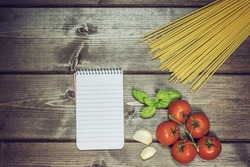 Blank notebook with lined paper, garlic cloves, basil leaves, spaghetti and tomatoes are lying on the wooden table. Edited as a vintage photo with dark edges.