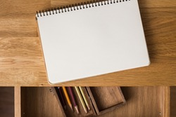 Blank notebook with pencils in box on the desk. Overhead view