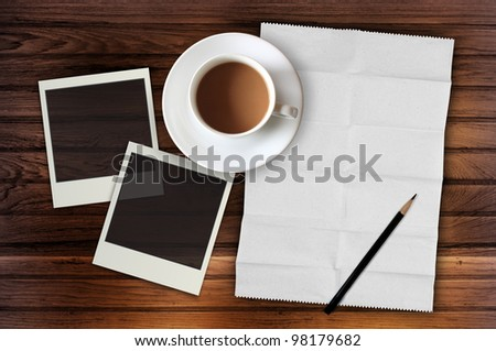 blank notebook with photo frame and coffee cup on wooden background