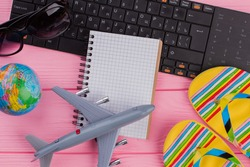 Blank notebook with woman's traveler accessories glasses wallet and flip-flops on pink table top background. Globe black keyboard grey airplane.