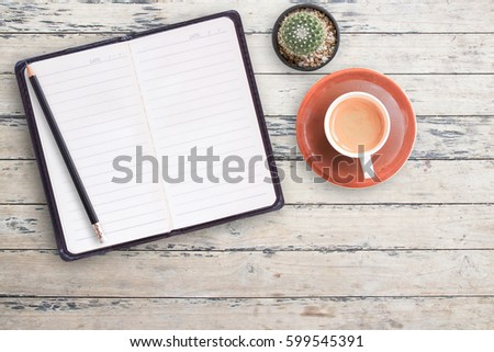Blank notebooks and black pencil with cup of coffee on wood table background. top view with copy space for design