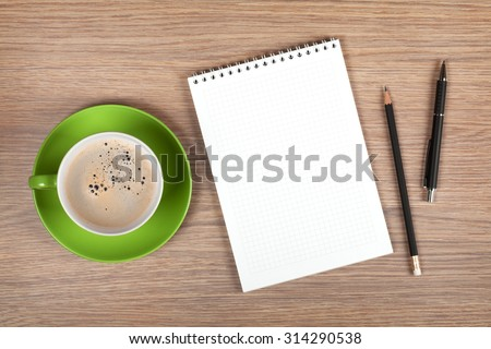 Blank notepad and coffee cup on office wooden table #314290538