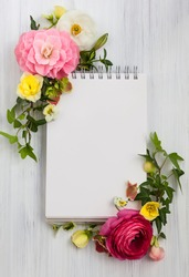 Blank notepad and flowers over white wooden background. Top view with copy space