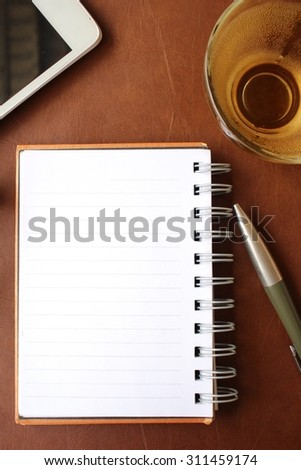 Blank notepad and smart phone with hot tea on office table #311459174
