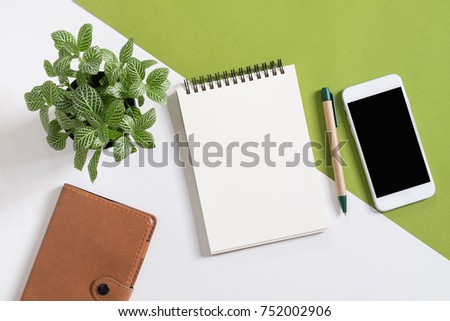 Blank notepad on with smart phone on desk.top view,flat lay
