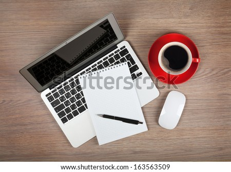 Blank notepad over laptop and coffee cup on office wooden table