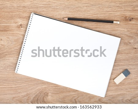 Blank Notepad, Pencil And Eraser On The Wooden Table. View From Above