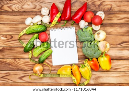 Blank notepad with different vegetables and measure tape on wooden background. Top view. Healthy food concept. #1171016044