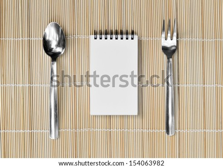Blank notepad with fork and spoon on bamboo mat background