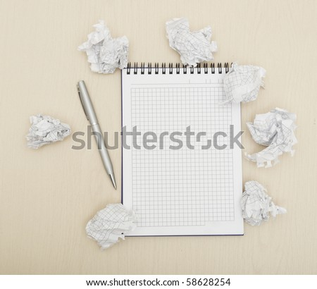 Blank notepad with ink pen on wooden desk