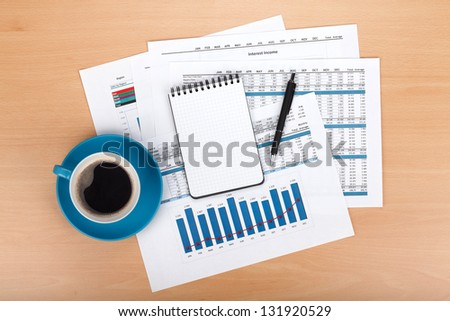 Blank notepad with pen and coffee cup over financial documents