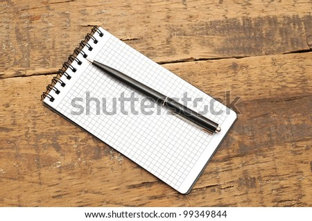 Blank notepad with pen on wood table