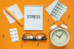 Blank of Notepad with the Word Stress, Pen, Clock and Antidepressants on orange Background. Top view, Flat lay. Copy space. Stop Depression. Education, Exam, Work Stress or Tension concept.