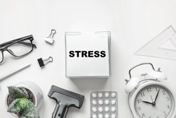 Blank of Notepad with the Word Stress, Pen, Clock and Antidepressants on white Background. Top view, Flat lay. Copy space. Stop Depression. Education, Exam, Work Stress or Tension concept.