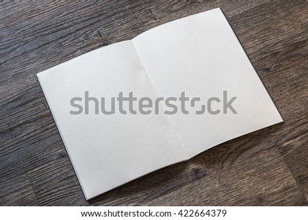 Blank open book, catalog, magazines, brochure, note template w/ paper texture on dark grey color wood table/ wooden floor background: Empty textured note book pages on timber backdrop for adding text