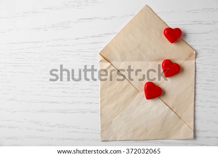 Blank open envelope with small hearts on wooden background #372032065