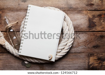 Blank open notebook on sea rope with bottle and ancient coins, on wooden table