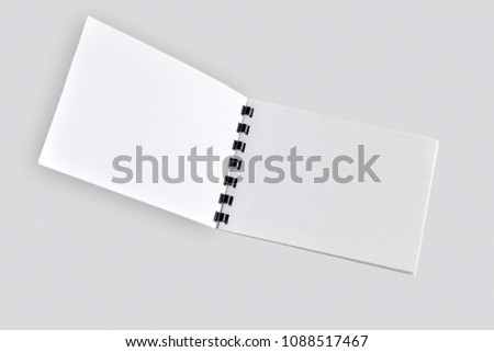 Blank open notebook or brochure with black plastic spiral close up, isolated on light gray. Diary notepad, paper page organizer or scrapbook - mock up for your design