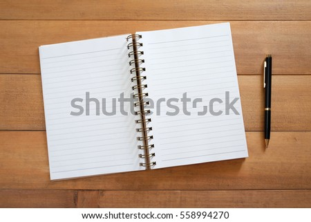 Blank open notebook with pen on wooden desk
