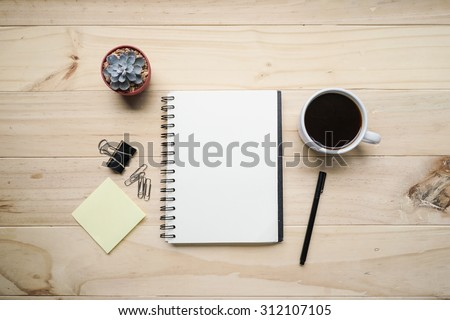 blank opened notebook with cup of coffee and memo note on wooden table. Top view. Writing concept