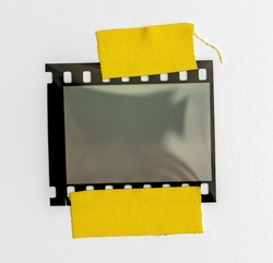 blank or empty 35mm dia film frame fixed by two yellow adhesive strips on white background, cool photo placeholder.