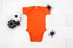 Blank orange baby bodysuit on white background with pumkins and spider decor, flat lay halloween newborn apparel mockup