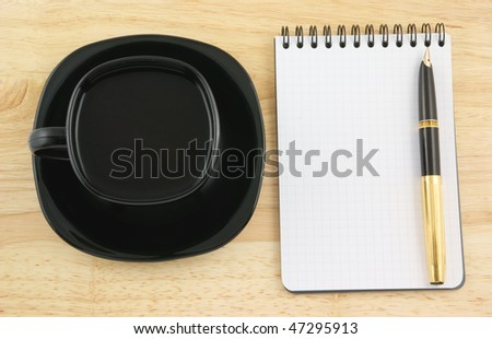 Blank pad of paper with pen and coffee on wooden background