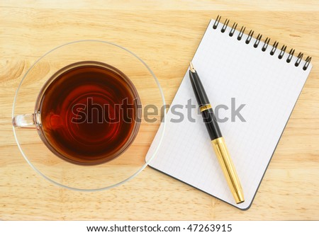 Blank pad of paper with pen and tea on wooden background