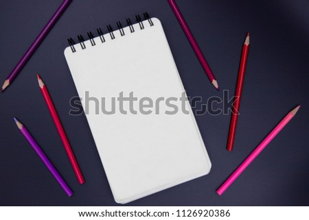 Blank page of vertical spiral sketching pad with pink and red pencil on black background, top view photo. Romantic Valentine handmade art banner background. Sketch or drawing mockup. Empty notebook #1126920386