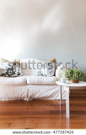 Blank painted grey wall with white country style sofa and coffee table