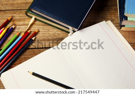 Blank paper and colorful pencils, on the wooden table. View from above. School concept.