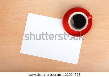 Blank paper and red coffee cup on wood table