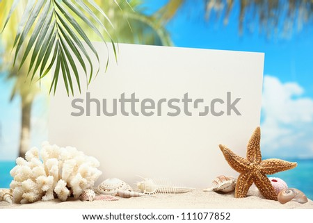 Blank paper card and seashells on sand beach.