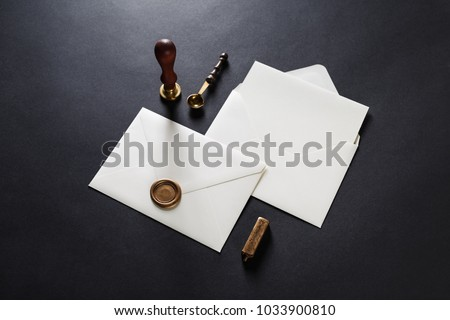 Blank paper envelopes with golden wax seal, stamp, spoon and postcard on black paper background. Mockup for your design.