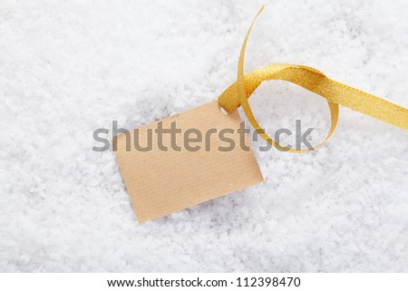 Blank paper gift label with a decorative golden ribbon on a bed of snow for your Christmas greeting