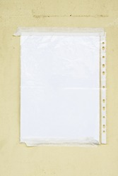 Blank paper in sleeve taped to a wall