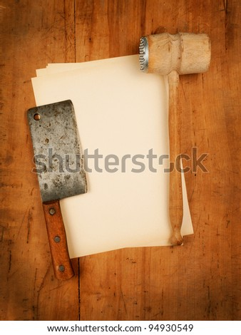 blank paper menu with old meat mallet and cleaver as background - stock photo