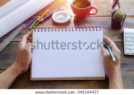 Blank paper note in female hand for any idea on desk work.